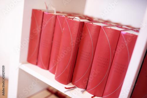 Valokuva  Rote evangelische Gesangbücher in einem weißen Bücherregal
