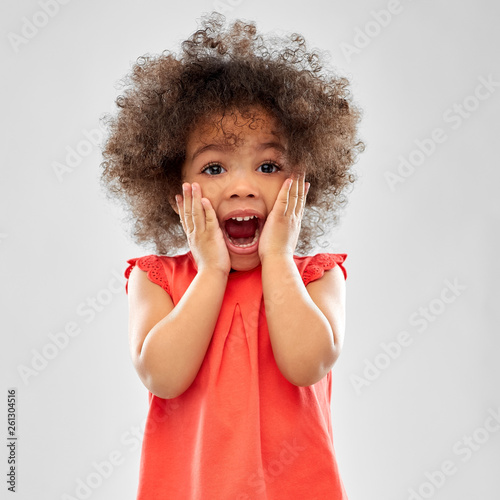 Fototapeta childhood and people concept - surprised or scared little african american girl screaming over grey background obraz na płótnie
