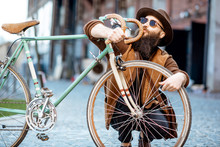 Portrait Of A Bearded Hipster Dressed Stylishly With Hat Hugging His Retro Bicycle Outdoors On The Urban Background