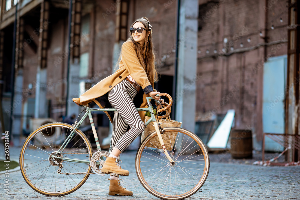 Fototapeta Full body portrait of a beautiful stylish woman dressed in coat standing with retro bicycle outdoors on the industrial urban background