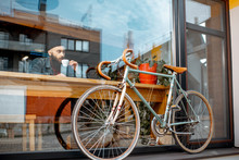 Stylish Man Enjoying Coffee Drink While Sitting At The Cafe Near The Window With Retro Bicycle. Wide View Through The Window