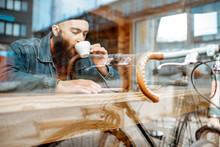 Stylish Man Enjoying A Coffee Drink While Sitting At The Cafe Near The Window With Retro Bicycle. View Through The Window With Urban Reflection