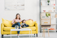 Attractive Woman With Adorable Son Resting On Yellow Sofa In Spacious Living Room