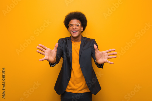 Fotografie, Obraz  Young business african american man over an orange wall very happy giving a hug