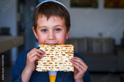 Photo Cute Caucasian Jewish boy holding in his hands and taking a bite from a traditional Jewish matzo unleavened bread