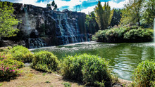 Wide Wall With Waterfall In A Public Nature Park In Guadalajara Jalisco Mexico On A Sunny Day With A Lake, Trees, Colorful Flowers And Lots Of Green Vegetation