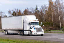 Long Haul White Big Rig Semi Truck Transporting Goods In Dry Van Semi Trailer Running On Straight Highway Road