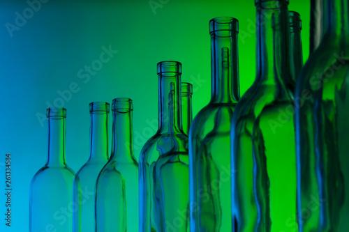 Glass wine bottle necks on green background Wallpaper Mural