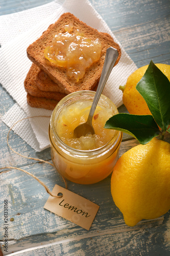 lemon jam in the glass jar with fruit around