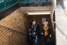 Two Friends Coming Up The Stairs And Out Of A Subway Station
