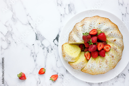 Classic vanilla bundt cake with strawberries and powdered sugar top view Fototapet