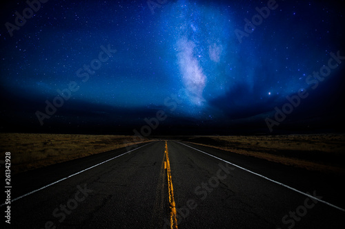 Photo sur Toile Autoroute nuit A highway disappearing into the distance illuminated by a star filled dramatic night sky in a rural landscape