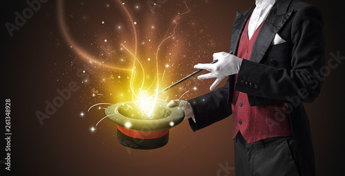 Vászonkép Magician hand conjure with wand  light from a black cylinder