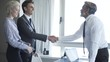 Medium shot of business people shaking hands in office