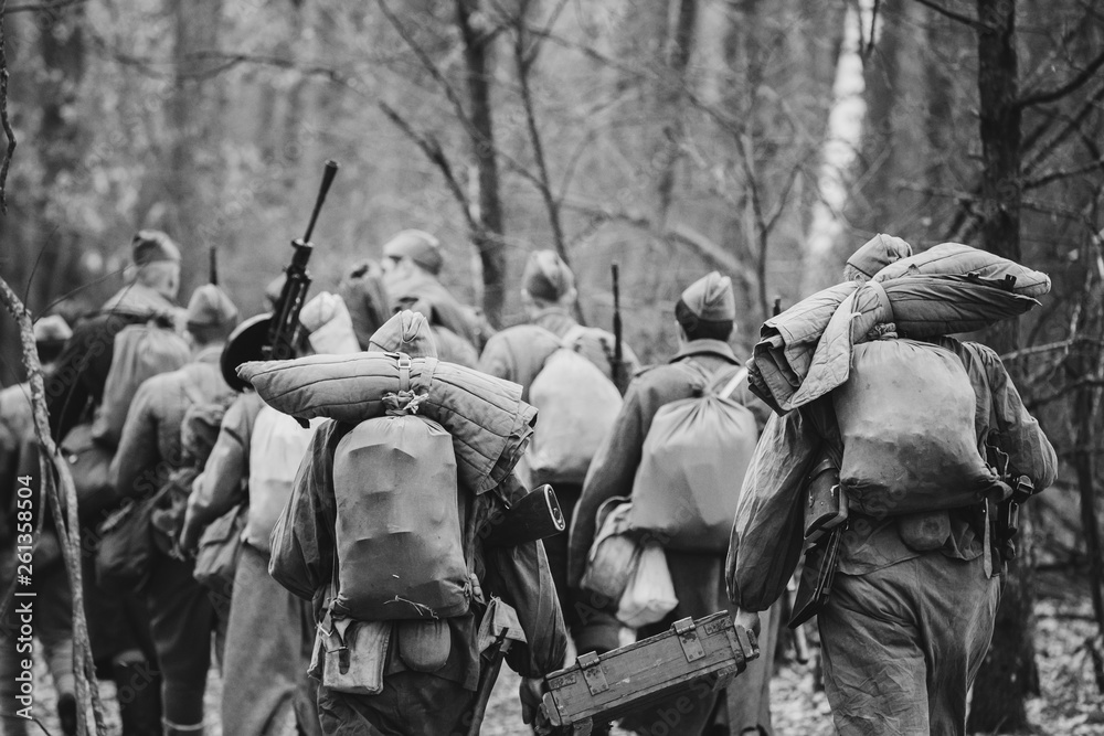 Fototapeta Re-enactors Dressed As World War II Russian Soviet Red Army Soldiers Marching Through Forest In Autumn Day. Photo In Black And White Colors. Soldier Of WWII WW2 Times