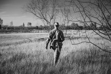 Re-enactor Dressed As World War II Russian Soviet Red Army Officer Soldier Walking Through Autumn Meadow. Photo In Black And White Colors. Soldier Of WWII WW2 Times