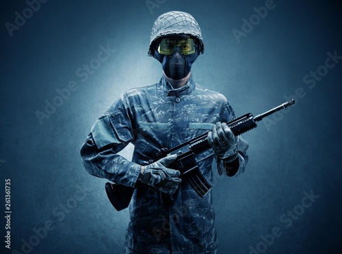 Valokuva  Soldier agent in a dark room with arms on his hand and gas mask