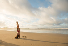 Side View Of Anonymous Female In Swimwear Performing Handstand On Wet Sand Near Sea Against Cloudy Sky