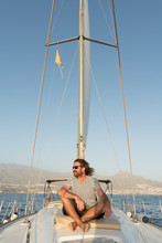 Positive Bearded Adult Male In Sunglasses Sitting Floating On Expensive Boat On Sea In Sunny Day