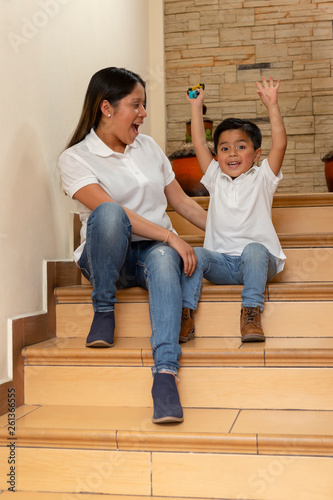 Valokuva  Latin mom having fun time whith her little son who has his hands up at home