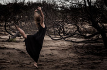 Young Ballerina In Black Wear With Stretched Out Hands Posing Between Dry Woods