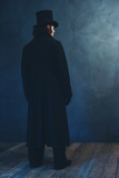Edwardian man in long black coat and hat standing towards grey wall. - 261373178