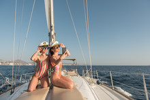 Beautiful Young Females In Sunglasses And Captain Hats Taking Selfie On Mobile Phone And Sitting On Deck Of Expensive Boat Floating On Water In Sunny Day