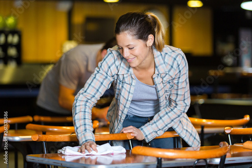 Photo beautiful barmaid cleaning table in a bar