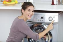 Woman Pressing Button To Start Washing Machine
