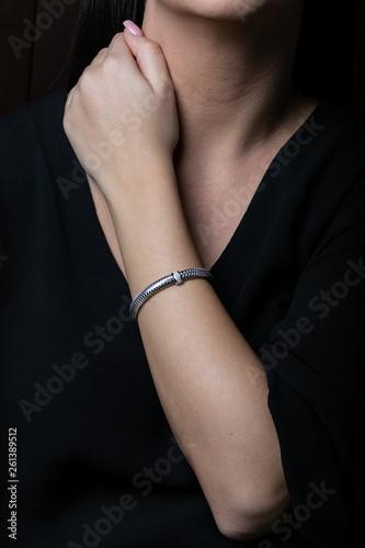 Fotografía  Female, silver, wicker, bracelet with diamonds in the middle on woman hand, on b