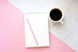 Business Workplace in a minimalist style with cup of coffee, notebook, pencil. Pink and marble background