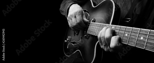 Obraz Guitarist hands and guitar close up. playing electric guitar. copy spaces.  black and white. - fototapety do salonu