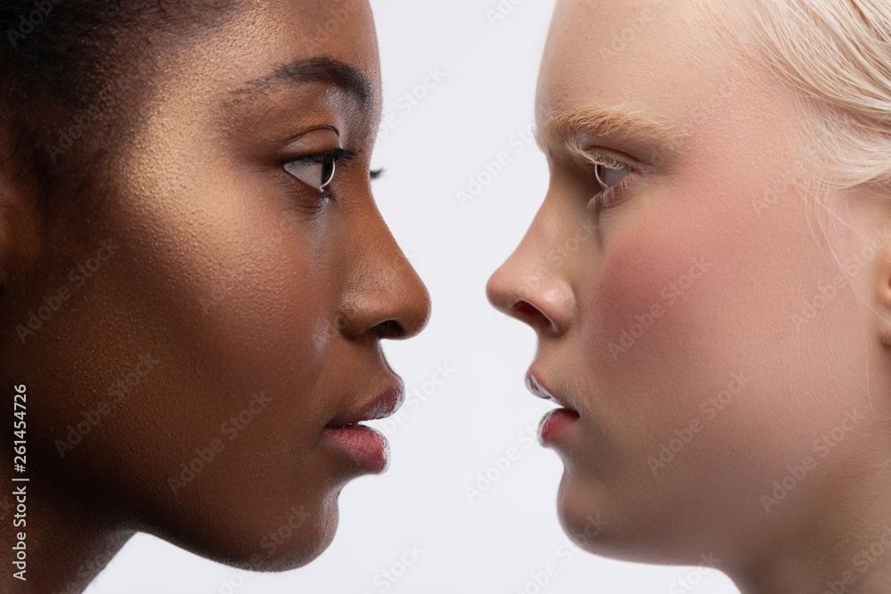 Fototapety, obrazy: Two young women with different skin color looking into eyes