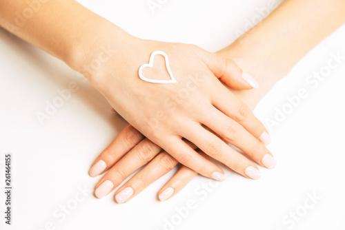 Fototapeta  Skincare cream in shape of heart on a female hand.