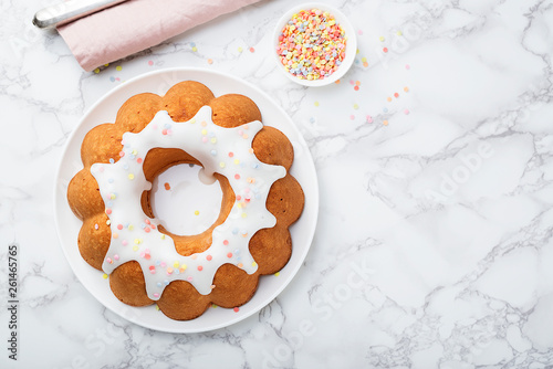 Fotografering Bundt Cake with Sugar Glaze and decorations on gray marble background