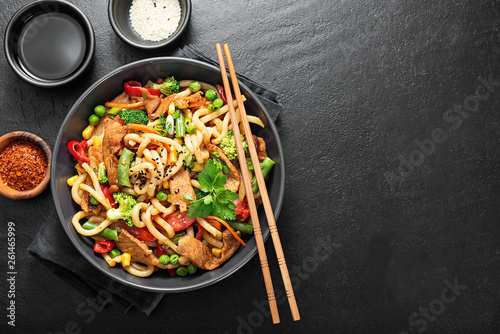 Valokuva  Udon stir fry noodles with pork meat and vegetables in a dark plate on black stone background