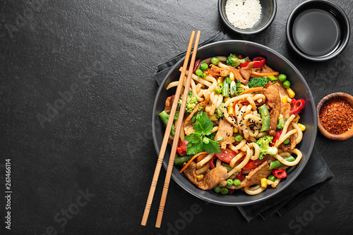 Fotografía  Udon stir fry noodles with pork meat and vegetables in a dark plate on black stone background