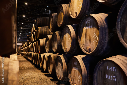 Old aged traditional wooden barrels with wine in a vault lined up in cool and da Fototapet