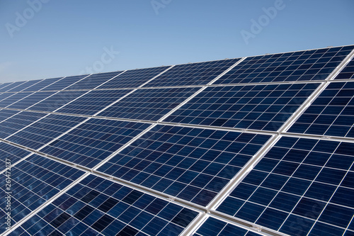 Obraz Close up clean solar panels on blue clear sky background producing friendly environment energy. Alternative electricity source - fototapety do salonu