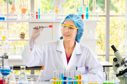 Fotografia  Scientists look at a cotton ball that is attached to a red chemical