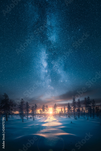 Ethereal fantasy image of sunset behind snowy forest landscape with epic milky way on the sky