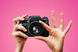 canvas print picture - Vintage Camera in female hand. A photo. Photographer. Manual focus. Colored background. Pink