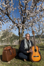 Overview Of Young Shaven Man With A Guitar And Old Suitcase Sitting On The Grass Under A Tree In A Sunny Day