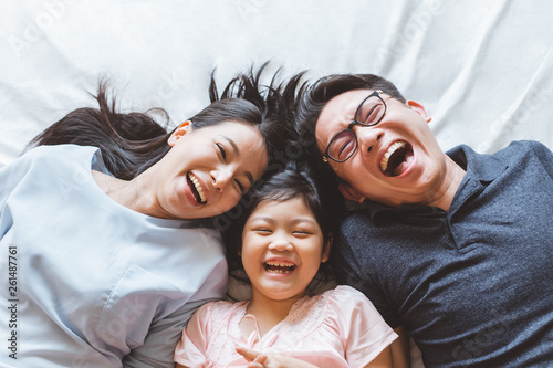 Fotomural  Happy Asian family laying on bed in bedroom with happy and smile, top view