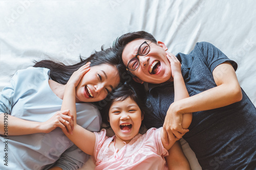 Obraz na plátne  Happy Asian family laying on bed in bedroom with happy and smile, top view