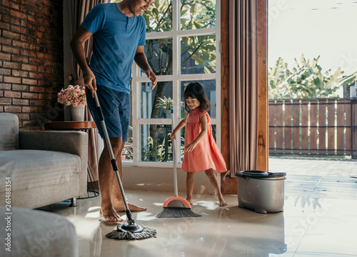 Tela little girl help her daddy to do chores at home