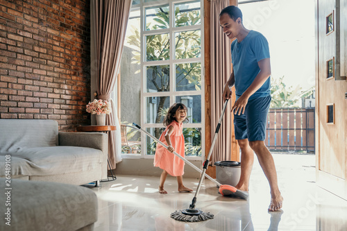 Fotografia little girl help her daddy to do chores at home