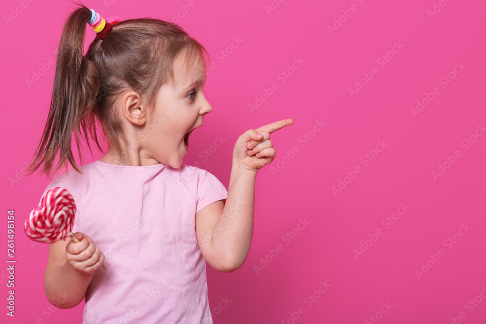 Fototapety, obrazy: Close up portrait of little attractive child opening mouth widely, looking other side with excitement, holding heart bright lollipop. Playful merry little fair haired girl spends sparetime happily.