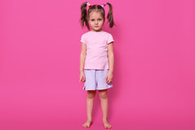 Tired Magnetic Small Girl With Pigtails Is Focused On Camera, Looks Serious, Wearing Light Pink T Shirt And Casual Shorts, Having Colourful Scrunchies In Her Hair. Childhood And Emotions Concept.