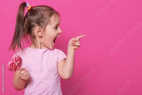 Close up portrait of little attractive child opening mouth widely, looking other side with excitement, holding heart bright lollipop. Playful merry little fair haired girl spends sparetime happily.